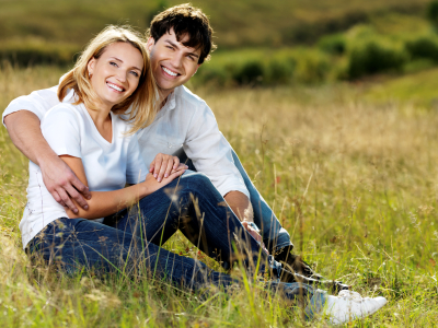 beautiful couple sitting in meadow